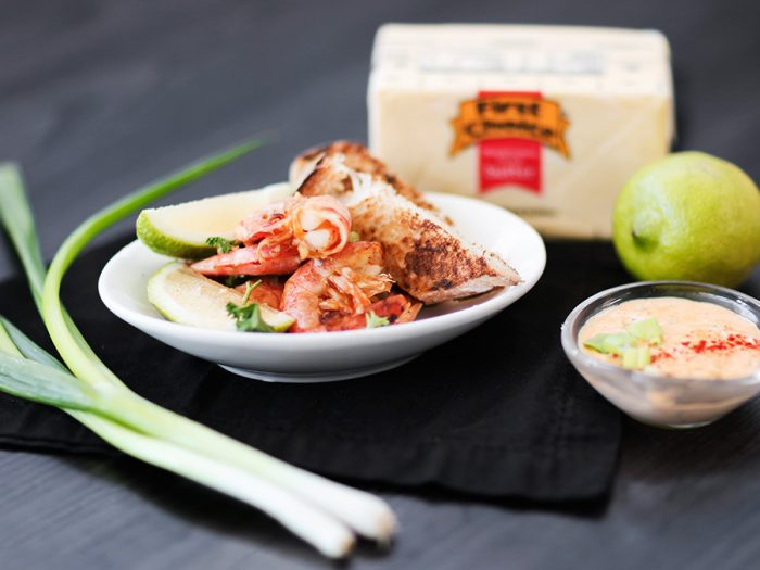 A single portion of buttery prawns served with peri peri sauce and toast.